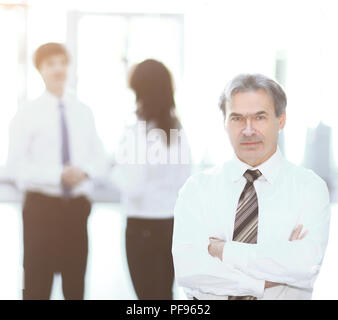 portrait of a senior businessman on blurred background office - Stock Photo