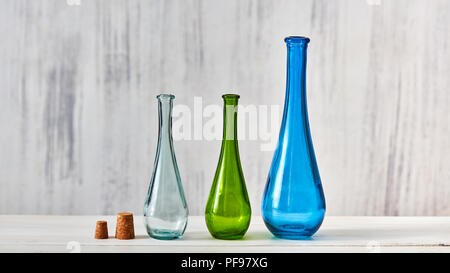 The bottles green, blue, transparent stand on a gray table on a light gray background with place for text. Concept of saving homemade products. - Stock Photo
