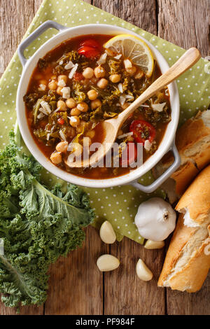 Stewed kale cabbage with chickpeas and vegetables close-up on the table. Vertical top view from above - Stock Photo