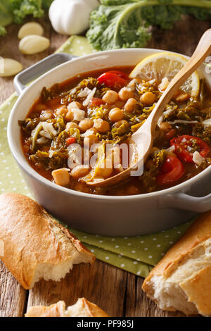 Stewed kale cabbage with chickpeas and vegetables close-up on the table. vertical - Stock Photo