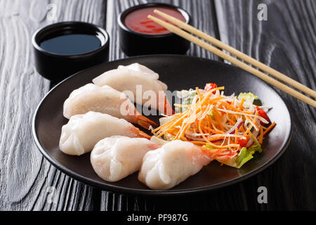 jiaozi, gyoza dumplings with prawns close-up served with vegetable and soy and tomato sauces on the table. horizontal - Stock Photo