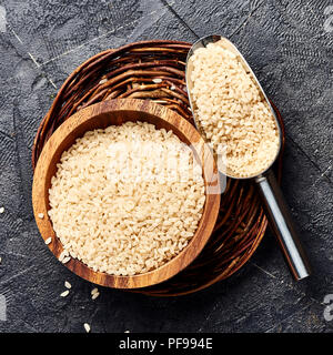 White rice in wooden bowl on black background. Top view of grains. - Stock Photo