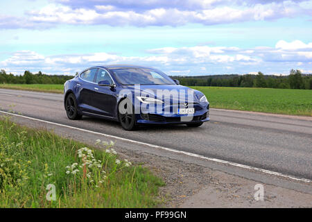 Blue Tesla Model S electric car of the updated exterior design at speed on highway in rural scenery on day of summer. Jamsa, Finland - June 14, 2018. - Stock Photo