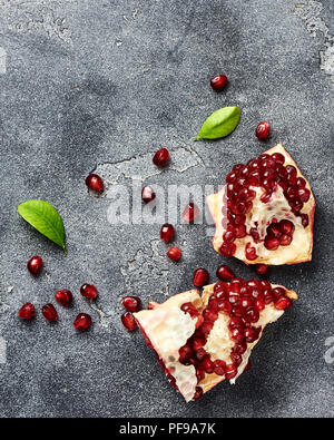 Pomegranate fruit with seeds on gray background with copy space. Top view. - Stock Photo