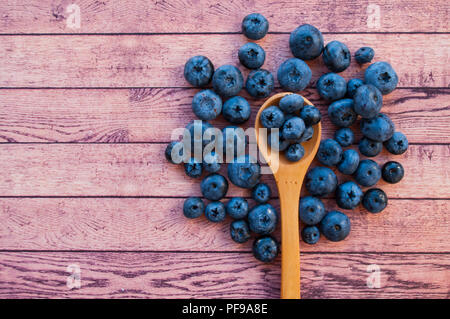 Fresh and juicy blueberries in a wooden spoon on wooden table with copyspace. Healthy food concept. - Stock Photo