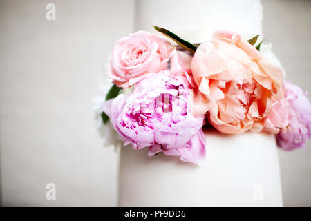 Closeup of modern white wedding cake with peony peonies decoration and negative space - Stock Photo