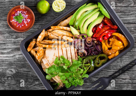 Delicious Chicken Fajita Platter with Avocado, Pita Bread,  Bell Pepper, Lime, Red Onion and Cilantro, bowl with salsa sauce, close up, top view - Stock Photo