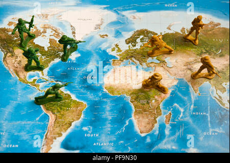 toy plastic soldiers armies facing each other on a world map - Stock Photo
