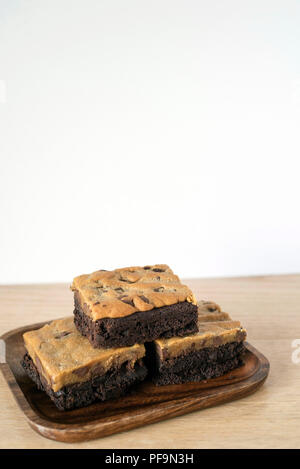 Rich Brookie Bars Stacked on a Wooden Plate in front of a Light Background - Stock Photo