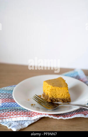 Half-Eaten Slice of Pumpkin Cheesecake on a Plate with a Fork - Stock Photo