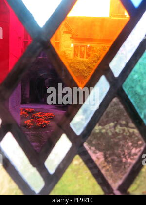 Close-up view of the coloured diamond-shaped panes of glass in the stained glass window, looking out to the courtyard; Baddesley Clinton, Warwickshire - Stock Photo