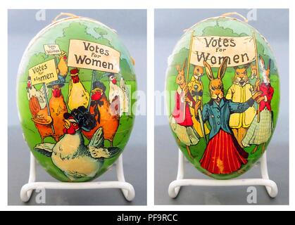 Large, colorful, paper mache box in the form of an egg, one side with rabbits wearing Edwardian dresses, the other with chickens wearing Edwardian women's hats, on each side the animals have fierce looks on their faces and hold one or more signs reading 'Votes for Women', 1900. () - Stock Photo