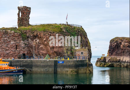 RNLI Lifeboat moored in harbour, with ruined Dunbar Castle, Dunbar, East Lothian, Scotland, UK - Stock Photo