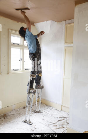 Buckingham, UK - May 07, 2015. A plasterer skims a high ceiling whilst standing on stilts. - Stock Photo