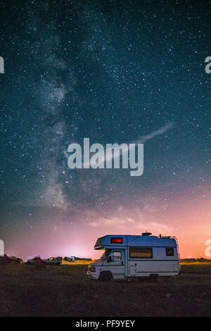 Camper van camping with the Milky way in the background - Stock Photo