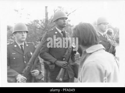 Black and white photograph, showing three, clean-shaven, male National Guardsmen, standing and holding guns, with the shaggy head of a bearded antiwar protestor visible in the foreground, photographed during the Vietnam War era in Washington, DC, United States, 1969. () - Stock Photo