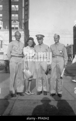 Black and white photograph showing a smiling young woman, wearing a skirt and holding a large clutch, standing between three smiling men dressed in military uniforms, all standing on a city street corner, in full-length view, photographed in Ohio, 1945. () - Stock Photo
