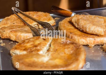 Close up macro of Balkan burek with cheese in bakery market. Traditional breakfast food in the Balkans. Selective focus - Stock Photo