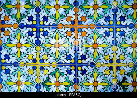 Brightly colored (orange, blue, and yellow) tiles with an ornate geometric floral pattern at Plaza de Espana in Seville, Andalusian Spain - Stock Photo