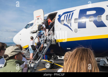 Passengers,travellers,boarding,Ryanair,Boeing,on,tarmac,at,Carcassonne,Airport,South,of,France,.Flight,to Stansted Airport,London,England,Europe, - Stock Photo