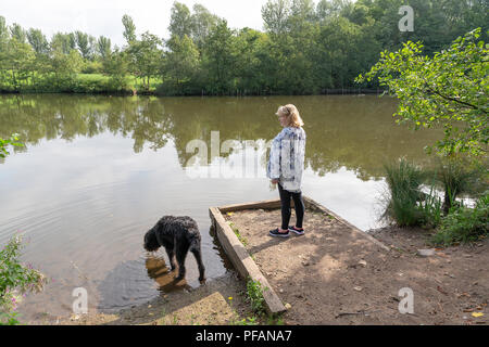 Mature blond lady stands at the side of the lake at Three Sisters Local Nature Reserve, Three Sisters Road, Ashton-In-Makerfield, Wigan with her black - Stock Photo