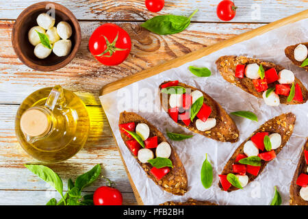 bruschetta with tomatoes, mini mozzarella and basil on fried in olive oil rye baguette with seeds, bottle with oil, tomatoes and mozzarella in small b - Stock Photo