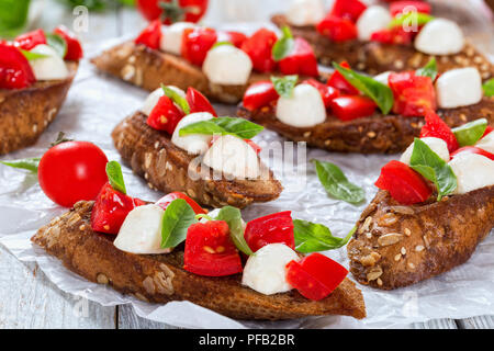 bruschetta with tomatoes, mozzarella and basil on fried in olive oil rye baguette with seeds, on parchment paper. close-up, top view, selective focus - Stock Photo