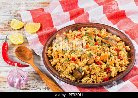 rice with meat, pepper, vegetables and spices on clay dish, kitchen towel,lemon slice, garlic, chili pepper and wooden spoon on white peeling paint pl - Stock Photo