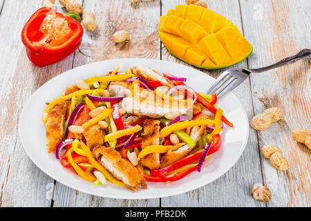 mango, bread crumbed chicken meat,  peanuts, bell pepper, red onion salad on white dish with half of  mango cutting in cubes, close-up - Stock Photo