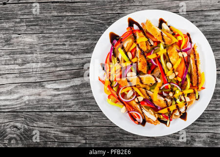mango, bread crumbed chicken meat,  peanuts, bell pepper, red onion salad on white dish with balsamic vinegar dressing, on old planks, blank space lef - Stock Photo