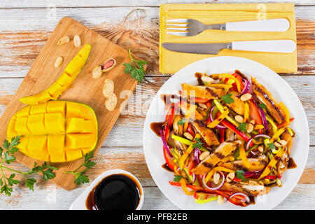 mango, bread crumbed chicken meat,  peanuts, bell pepper, red onion salad on white dish, balsamic vinegar dressing, old boards,  top view - Stock Photo