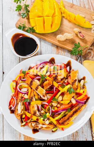 mango, bread crumbed chicken meat,  peanuts, bell pepper, red onion salad on white dish, balsamic vinegar dressing, old boards,  selective focus - Stock Photo