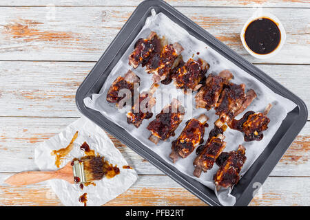 delicious sticky ribs seasoned with a spicy garlic ginger barbecue sauce prepared for grill in roasting pan on white peeling paint planks with basting - Stock Photo