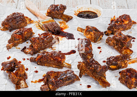 delicious hot sticky ribs seasoned with spicy soy garlic ginger barbecue sauce  on parchment paper with brush on wooden peeling paint background, top  - Stock Photo