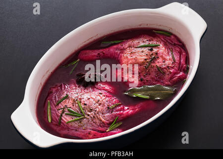 raw duck legs preparing for roasting, marinated in red wine with rosemary and spices in dish on black tabletop, view from above, close-up - Stock Photo