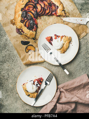 Flat-lay of plum galetta sweet cake pieces in white plates - Stock Photo