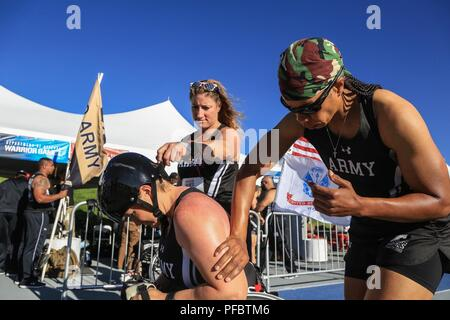U.S. Army Staff Sgt. Altermese Kendrick and Sgt. 1st Class Heather Moran, Team Army Competitors, help Staff Sgt. Tiffany Rodriguez-Rexroad put on sunscreen, Colorado Springs, Colorado June 01, 2018. The DoD Warrior Games is an adaptive sports competition for wounded, ill and injured service members and veterans. Approximately 300 athletes representing teams from the Army, Marine Corps, Navy, Air Force, Special Operations Command, United Kingdom Armed Forces, Canadian Armed Forces, and the Australian Defense Force will compete June 1 – June 9 in archery, cycling, track, field, shooting, sitting - Stock Photo