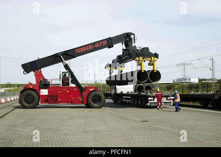 Russia. 21st Aug, 2018. Two 12.2-metre long and about 12-ton heavy pipe joints for the Nord Stream pipeline are loaded onto waiting trucks with a so-called ''reach stacker''. The pipe segments are then transported to the interim stock yard only a few hundred metres away. Since May 2008, one to three trains arrive every weekday in Mukran (Rgen Island, Germany) carrying up to 108 joints each. Credit: Nord Stream Ag/Russian Look/ZUMA Wire/Alamy Live News - Stock Photo