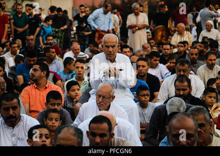 Gaza City, Gaza Strip, Palestinian Territory. August 21, 2018 - Palestinian Muslims perform the Eid al-Adha prayers in the Barcelona Park in the Tal al-Hawa district in the southern part of Gaza City. Eid al-Adha, or the Feast of the Sacrifice, is one of the holiest holidays for Muslims and is celebrated in Gaza in spite of the economic deterioration and Israeli blockade on the Strip and the recent escalation of tension with Israel. Credit: ZUMA Press, Inc./Alamy Live News - Stock Photo