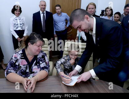 Veliky Novgorod, Russia. 21st Aug, 2018. VELIKY NOVGOROD, RUSSIA - AUGUST 21, 2018: Born with a congenital hand malformation, Maria Gaidukova (R seated), 9, with mother receive a modular bionic prosthetic hand after two weeks of tests; developed by Veliky Novgorod's Tekhbionik scientific research company led by engineer Stanislav Muravyov (R front), and unparalleled in Russia, the prosthesis features three different grip patterns controlled by electrical impulses in an operator's muscles. Alexander Demianchuk/TASS Credit: ITAR-TASS News Agency/Alamy Live News - Stock Photo