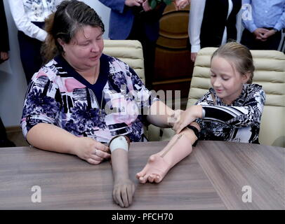 Veliky Novgorod, Russia. 21st Aug, 2018. VELIKY NOVGOROD, RUSSIA - AUGUST 21, 2018: Born with a congenital hand malformation, Maria Gaidukova (R), 9, with mother receive a modular bionic prosthetic hand after two weeks of tests; developed by Veliky Novgorod's Tekhbionik scientific research company led by engineer Stanislav Muravyov (not pictured), and unparalleled in Russia, the prosthesis features three different grip patterns controlled by electrical impulses in an operator's muscles. Alexander Demianchuk/TASS Credit: ITAR-TASS News Agency/Alamy Live News - Stock Photo