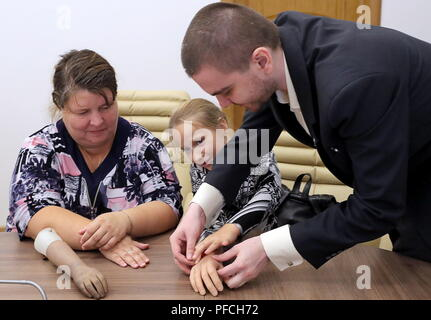 Veliky Novgorod, Russia. 21st Aug, 2018. VELIKY NOVGOROD, RUSSIA - AUGUST 21, 2018: Born with a congenital hand malformation, Maria Gaidukova (C), 9, with mother receive a modular bionic prosthetic hand after two weeks of tests; developed by Veliky Novgorod's Tekhbionik scientific research company led by engineer Stanislav Muravyov (R), and unparalleled in Russia, the prosthesis features three different grip patterns controlled by electrical impulses in an operator's muscles. Alexander Demianchuk/TASS Credit: ITAR-TASS News Agency/Alamy Live News - Stock Photo