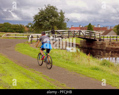 Glasgow, Scotland, UK. 21st  August, 2018. UK Weather: Cloudy sky as a change in weather is forecast through the day.A cyclist on the Forth and Clyde canal tow path near a  bascule bridge   at  Linnvale  Great Western Road. Credit: gerard ferry/Alamy Live News - Stock Photo