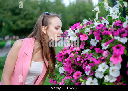 Side profile of young woman smelling blossoms - Stock Photo