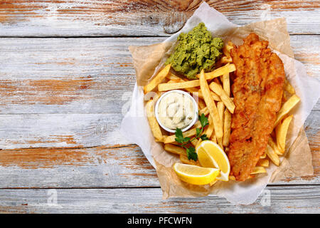 delicious crispy fish and chips - fried cod, french fries, lemon slices, tartar sauce and mashed peas on plate on paper on old wooden tabletop, authen - Stock Photo