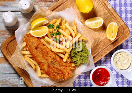 crispy fish and chips - fried cod, french fries, lemon slices, tartar sauce and mashed peas on plate on paper on old wooden table with rosemary in mor - Stock Photo