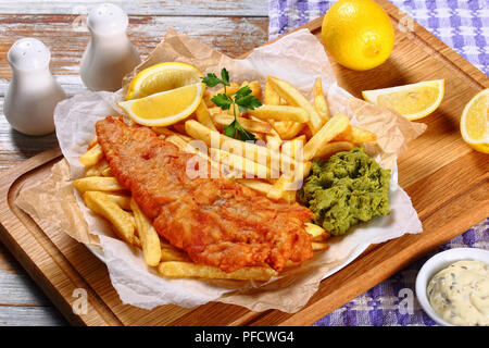 delicious crispy fish and chips - fried cod, french fries, lemon slices, tartar sauce and mushy peas on plate on paper. parsley and lemon wedges on wo - Stock Photo