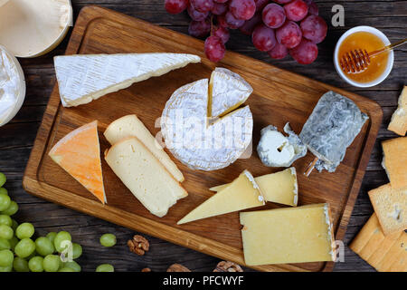 authentic french Cheeses served with grapes, honey and nuts on wooden background with triangle and round wooden containers made from poplar for packag - Stock Photo
