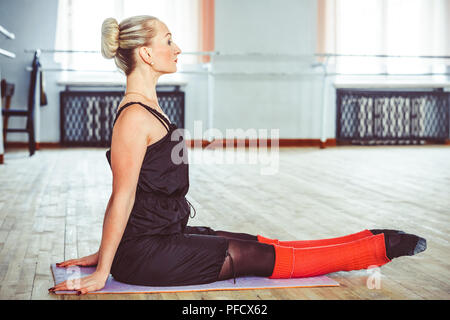 the dancer makes the warm-up in the ballet hall - Stock Photo