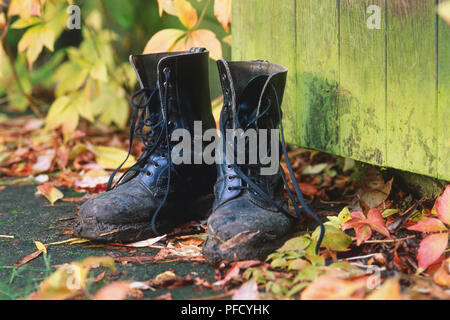 Pair of men's black lace-up leather boots, mud covering leather, on ground, autumnal leaves surrounding, green painted wooden door in background. - Stock Photo